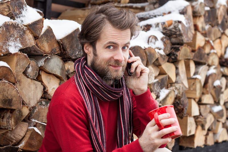 Szczęśliwy mężczyzna opowiada na telefonie komórkowym plenerowym podczas zimy zdjęcia royalty free