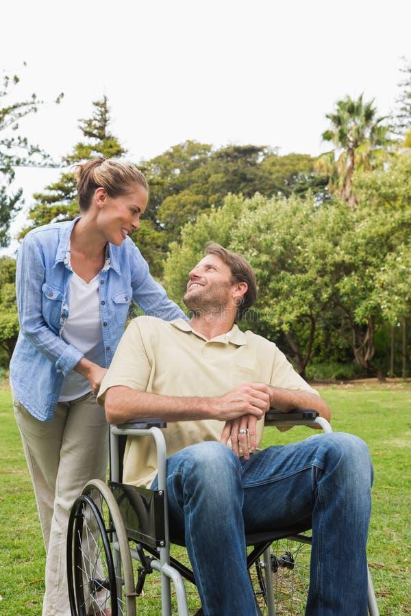 Szczęśliwy mężczyzna opowiada z partnerem w wózku inwalidzkim obrazy stock
