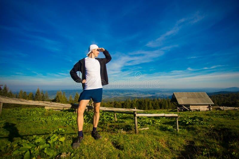 Szczęśliwy mężczyzna podziwia pięknego dolinnego widok w lecie na górze góry zdjęcia stock