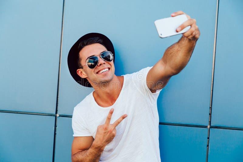 Szczęśliwy mężczyzna pokazuje pokoju znaka podczas gdy brać selfie, outdoors obrazy royalty free