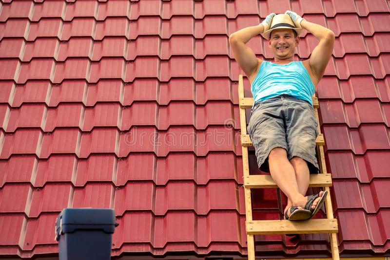 Szczęśliwy mężczyzna pozuje na schodkach przeciw tłu dach dom obrazy stock