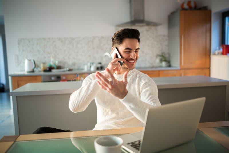 Szczęśliwy mężczyzna pracuje w domu opowiadać na wiszącej ozdobie obraz royalty free