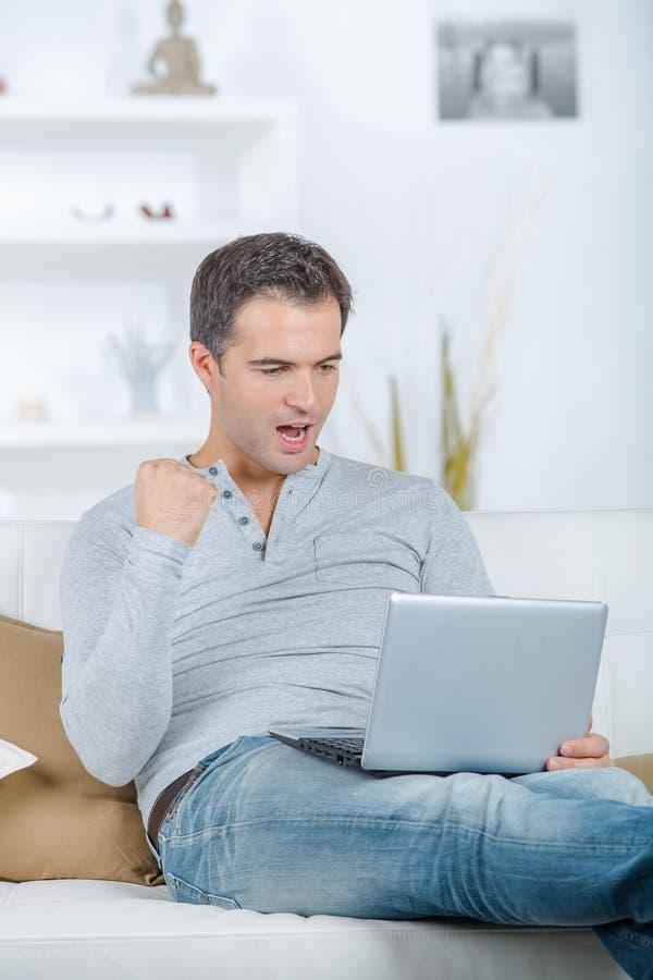 Szczęśliwy mężczyzna pracuje z laptopem w biurze fotografia royalty free