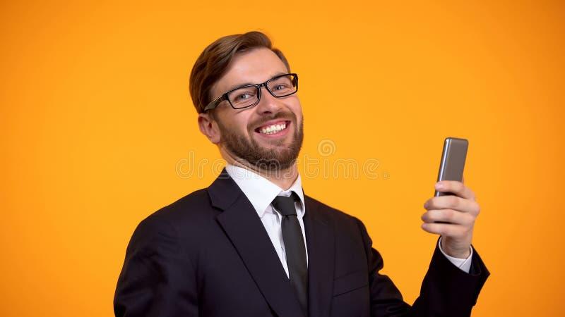 Szcz??liwy m??czyzna szczerze u?miecha si? mienia smartphone w r?ce, korzystnie kredytowanie, app obrazy stock