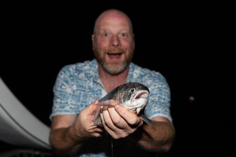 Szczęśliwy mężczyzna trzyma świeżego złapanego kokanee łososiowy zdjęcie stock
