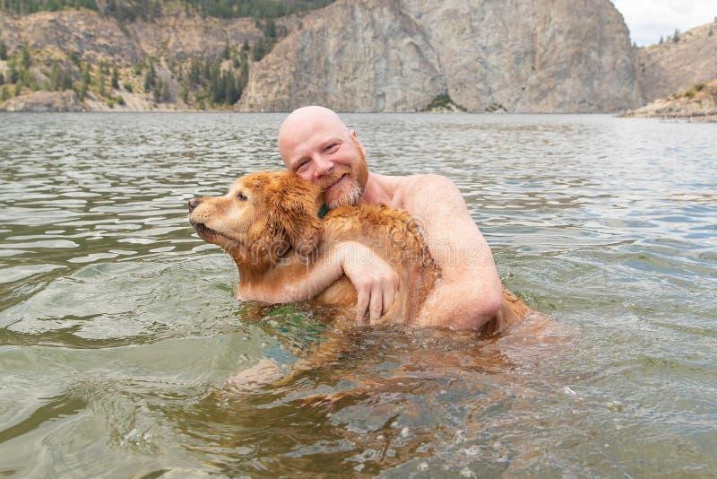 Szczęśliwy mężczyzna trzyma jego golden retriever psa podczas gdy pływający w wodzie obrazy stock
