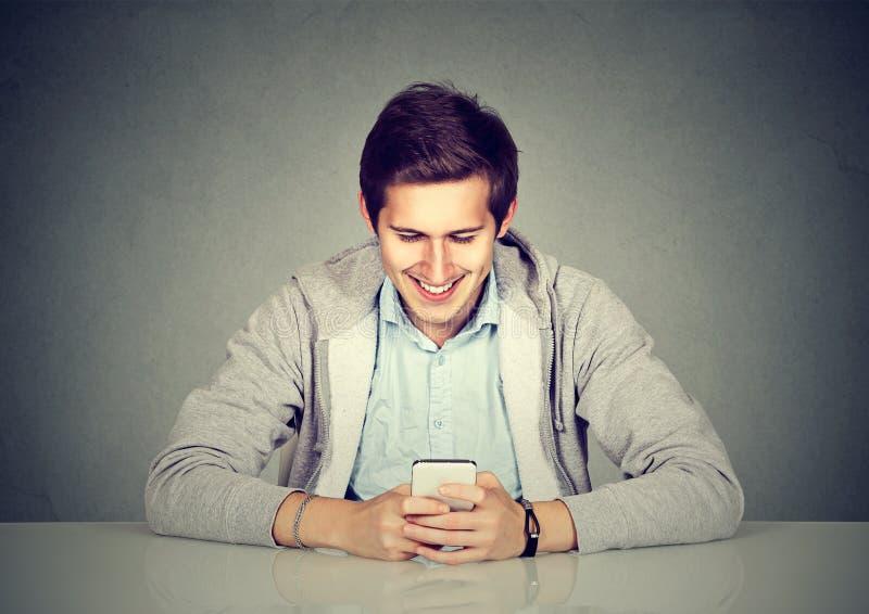 Szczęśliwy mężczyzna używa telefonu komórkowego obsiadanie przy stołem zdjęcia royalty free