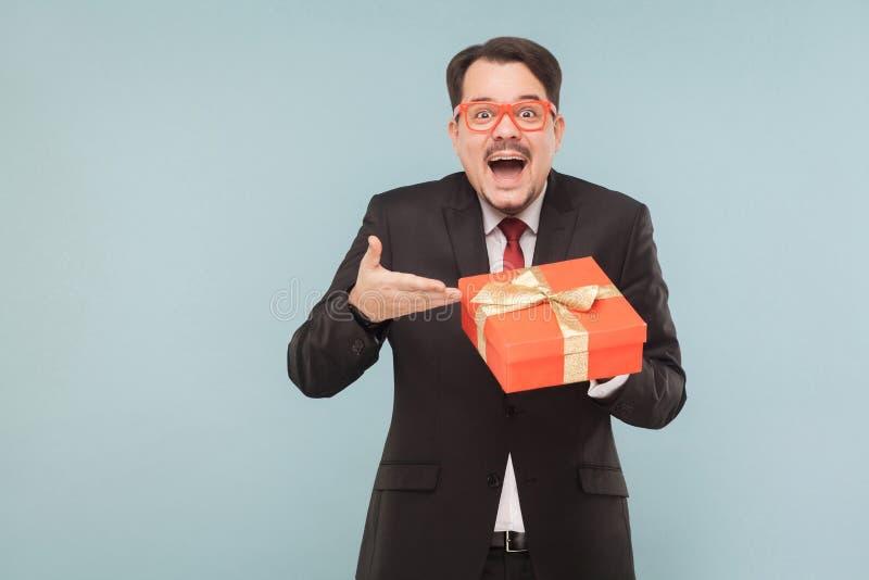 Szczęśliwy mężczyzna w czarnego kostiumu mienia prezenta czerwonym pudełku i patrzeć przychodziliśmy obraz royalty free