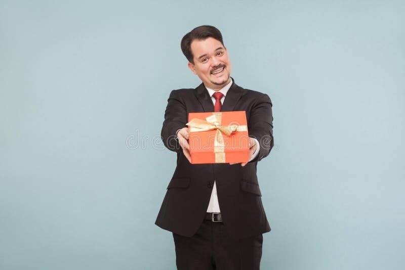 Szczęśliwy mężczyzna w czarnym kostiumu mieniu, dawać czerwonemu prezenta pudełku i zdjęcie royalty free