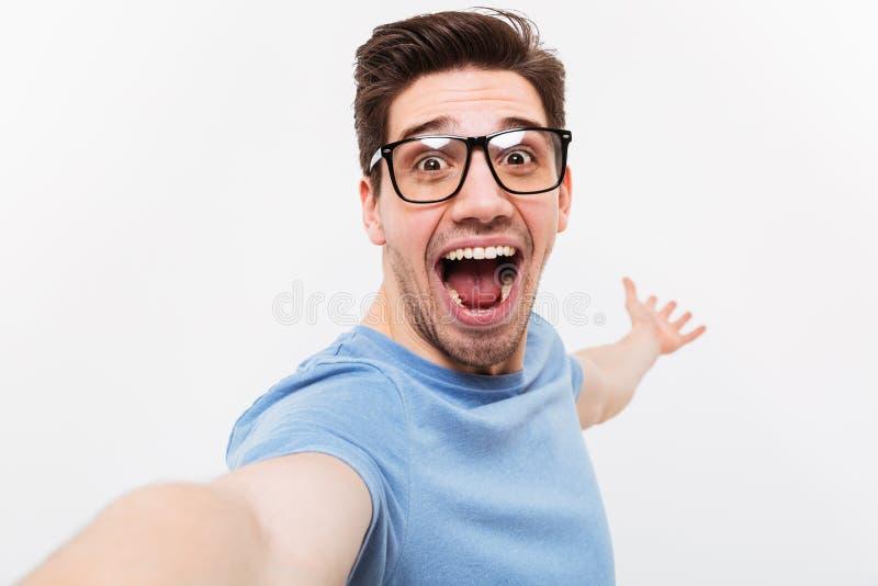 Szczęśliwy mężczyzna w koszulce i eyeglasses robi selfie i teraźniejszość obrazy royalty free