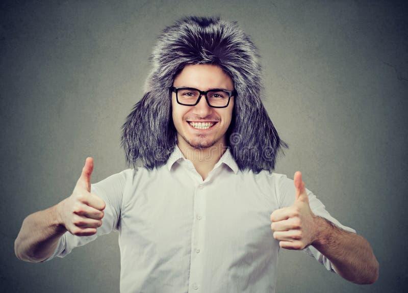 Szczęśliwy mężczyzna w zimy mienia kapeluszowych aprobatach fotografia stock