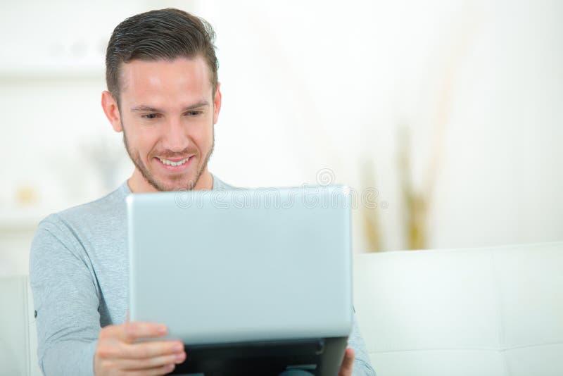Szczęśliwy mężczyzna z laptopem indoors obraz royalty free
