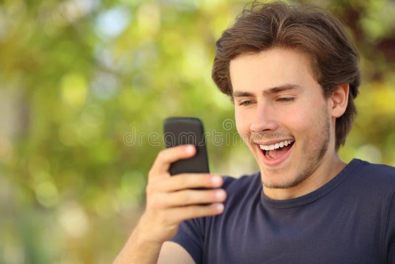 Szczęśliwy mężczyzna zaskakiwał patrzeć mądrze telefon zdjęcie royalty free