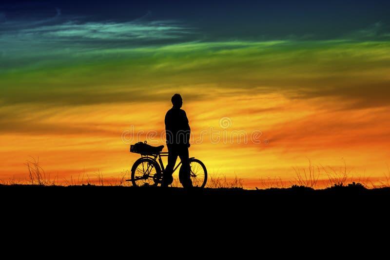 Szczęśliwy mężczyzna zmierzch, bicykl i zdjęcie stock