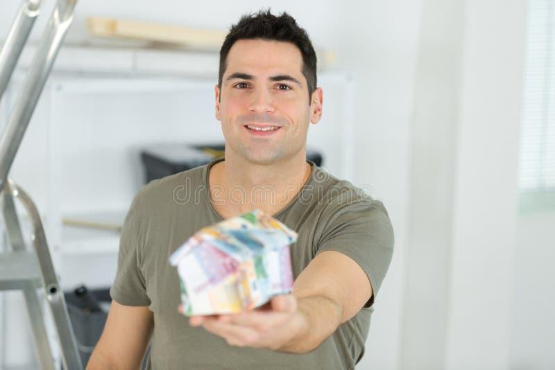 Szczęśliwy mężczyzny mienia atrapy dom obrazy royalty free