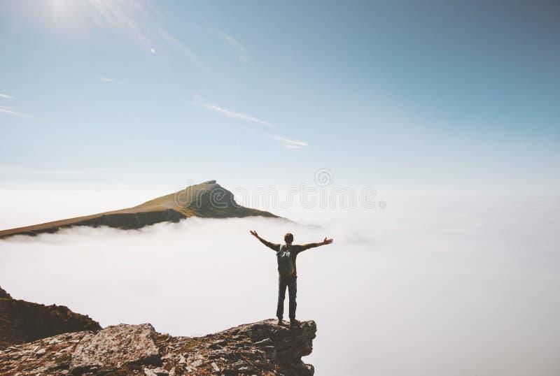 Szczęśliwy mężczyzny podróżnik stoi samotnie na falezy krawędzi górze nad chmurami obraz stock