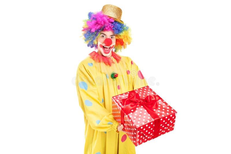 Szczęśliwy męski błazen trzyma czerwoną teraźniejszość zdjęcie stock