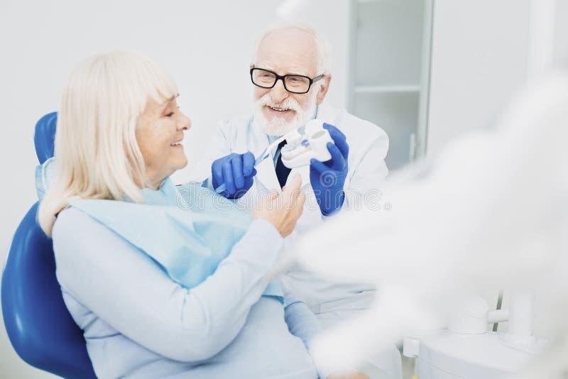 Szczęśliwy męski dentysta poleca traktowanie obrazy stock