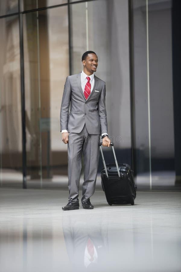 Szczęśliwy męski kierownictwo z bagażem na podróży służbowej zdjęcie stock