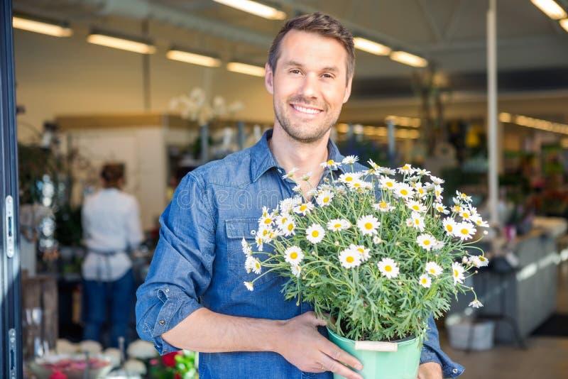 Szczęśliwy Męski klient Trzyma Kwiatonośne rośliny W sklepie zdjęcie royalty free