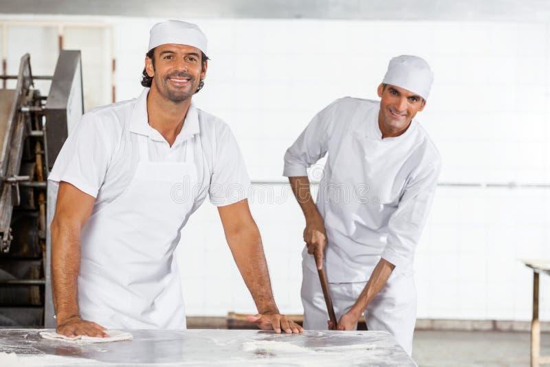 Szczęśliwy Męski piekarz W Jednolitej Cleaning piekarni obraz royalty free