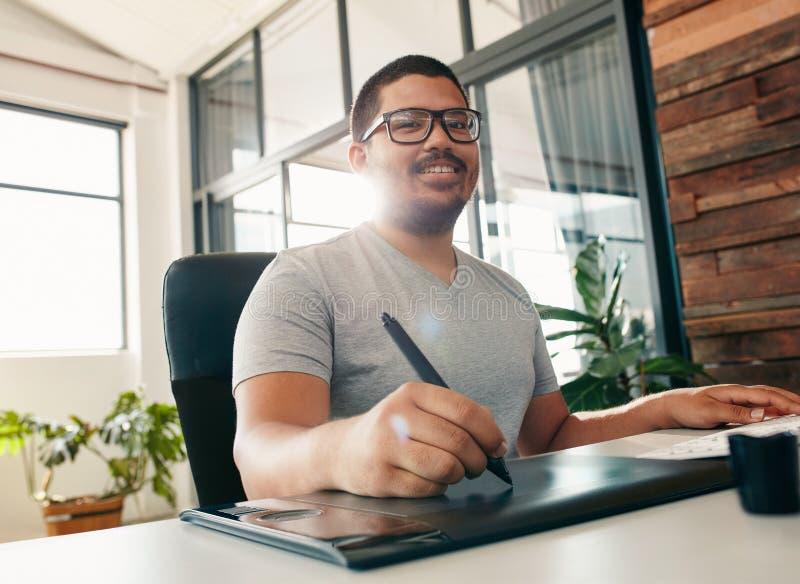 Szczęśliwy męski projektant pracuje w biurze fotografia royalty free