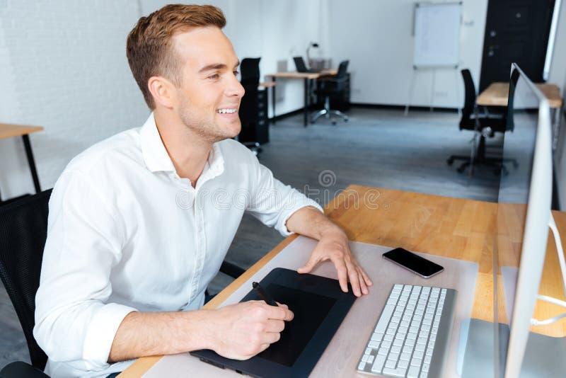 Szczęśliwy męski projektant używa komputerową i graficzną pastylkę w biurze fotografia royalty free