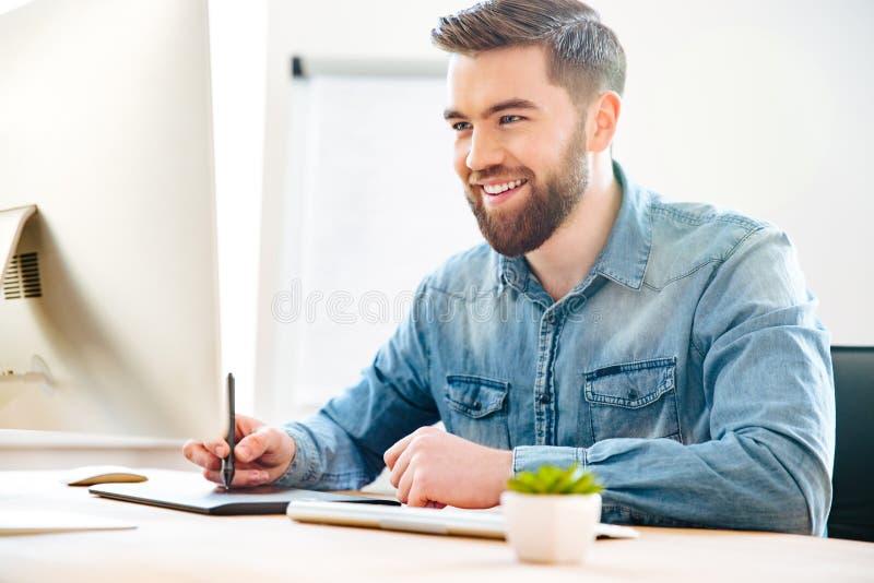 Szczęśliwy męski projektanta obsiadanie, rysunek na graficznej pastylce i obraz stock
