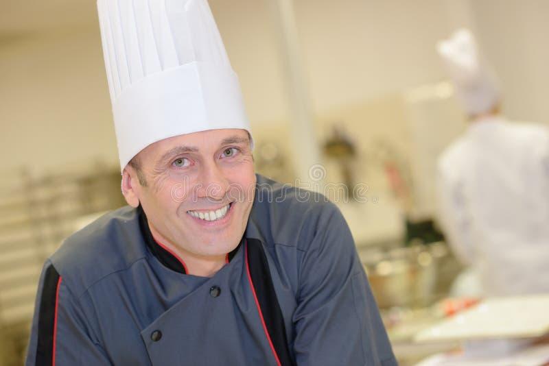 Szczęśliwy męski szef kuchni pozuje w restauracyjnej kuchni obraz royalty free