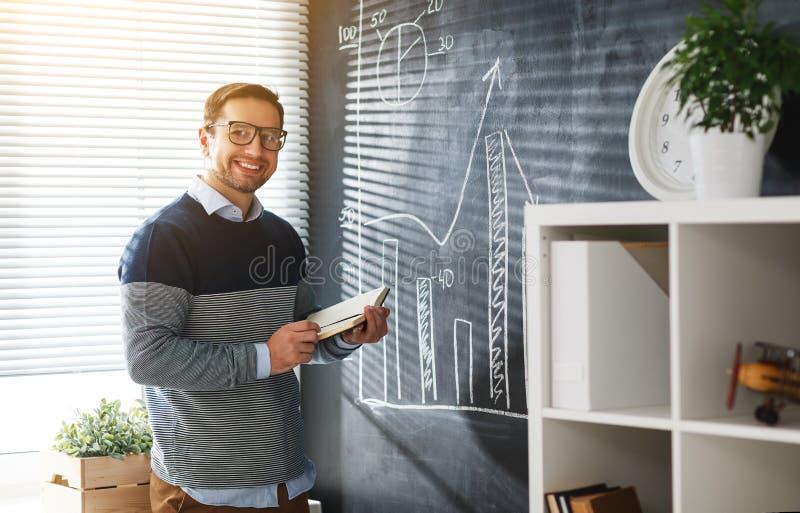 Szczęśliwy męski uczeń, nauczyciel, freelancer z kredą przy blackboard zdjęcie royalty free