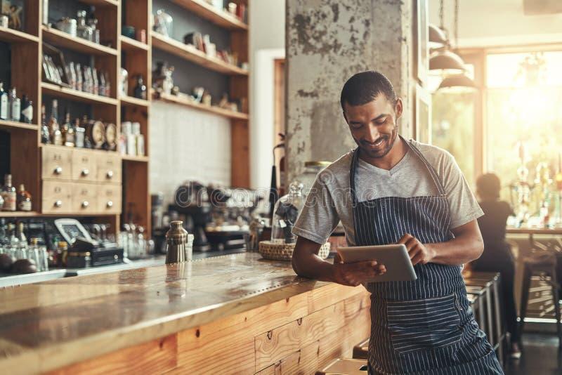 Szczęśliwy męski właściciel kawiarnia używać cyfrową pastylkę obraz royalty free