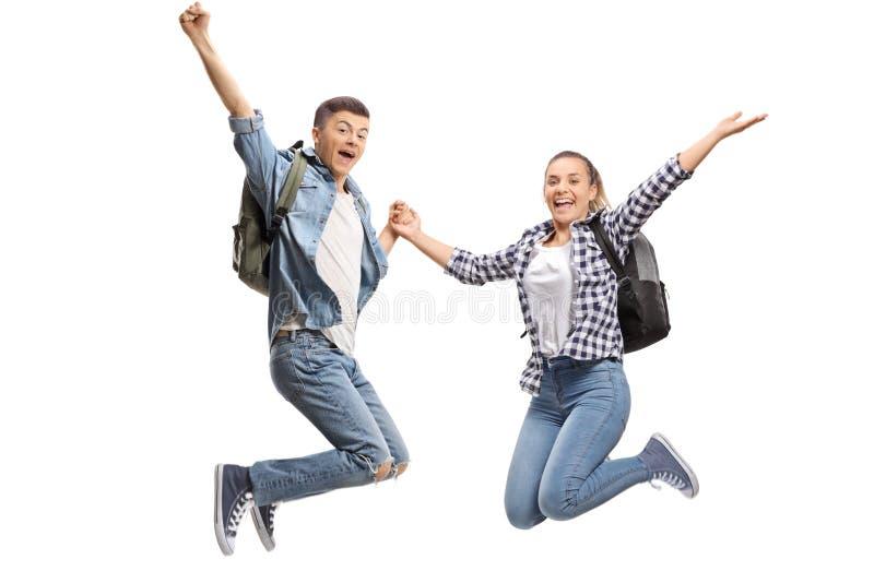Szczęśliwy męskich i żeńskich uczni skakać zdjęcia royalty free