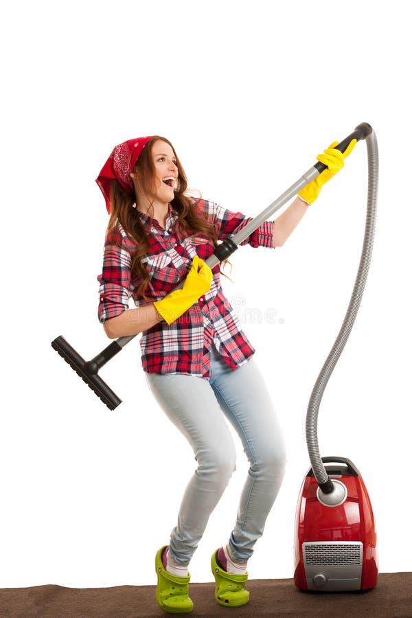 Szczęśliwy młoda kobieta śpiew gdy czyści z próżniowym cleaner obraz royalty free