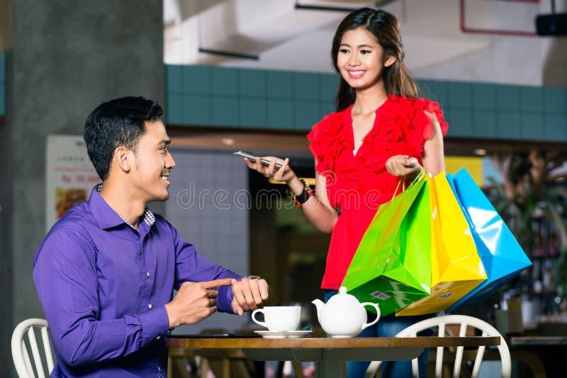 Szczęśliwy młodego człowieka czekanie dla jego pięknej dziewczyny po robić zakupy obraz royalty free