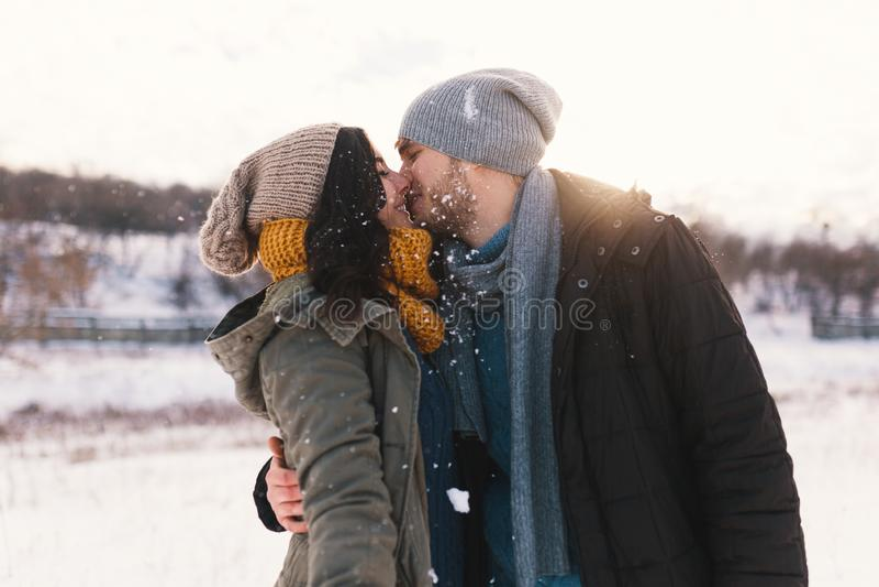 Szczęśliwy młodego człowieka i kobiety całowanie w zimie cieszy się życie i fotografia stock