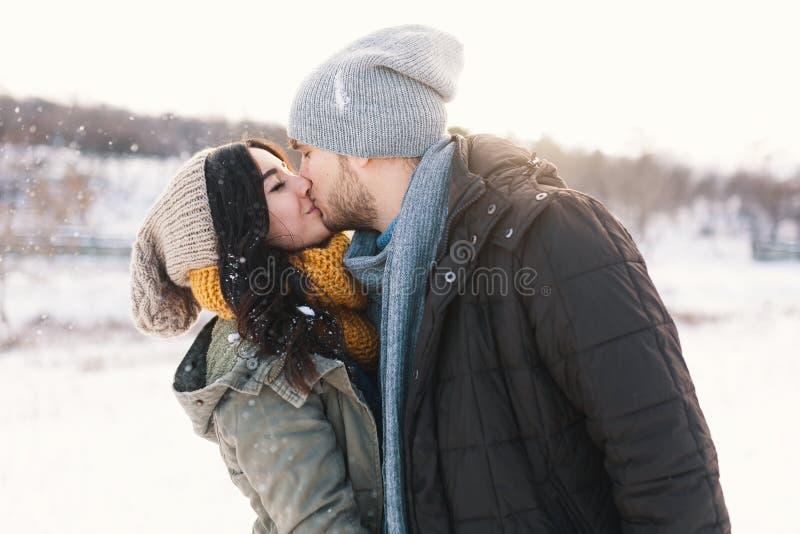Szczęśliwy młodego człowieka i kobiety całowanie w zimie cieszy się życie i zdjęcie royalty free