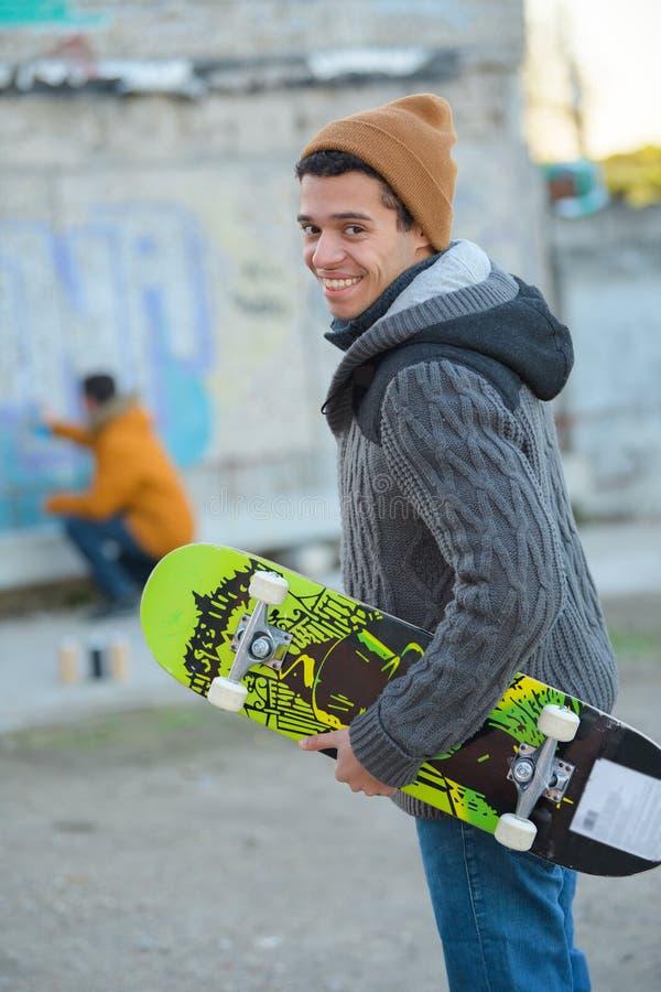 Szczęśliwy młodego człowieka jeździć na deskorolce zdjęcie stock