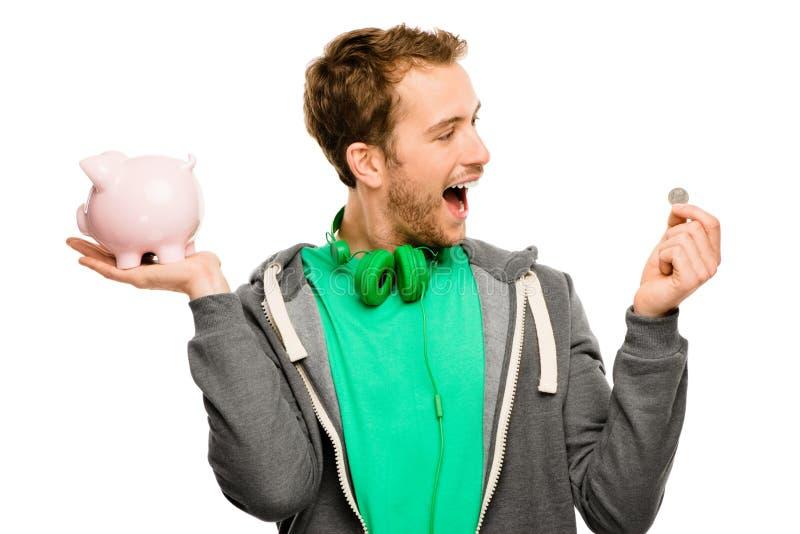 Szczęśliwy młodego człowieka kładzenia pieniądze w prosiątko banku odizolowywającym na bielu obrazy stock
