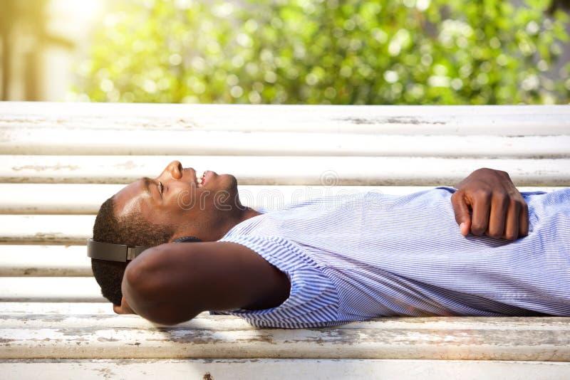Szczęśliwy młodego człowieka lying on the beach na parkowej ławce z hełmofonami zdjęcie stock