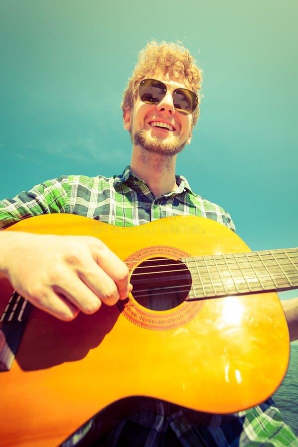 Szczęśliwy młodego człowieka modniś bawić się gitarę fotografia stock
