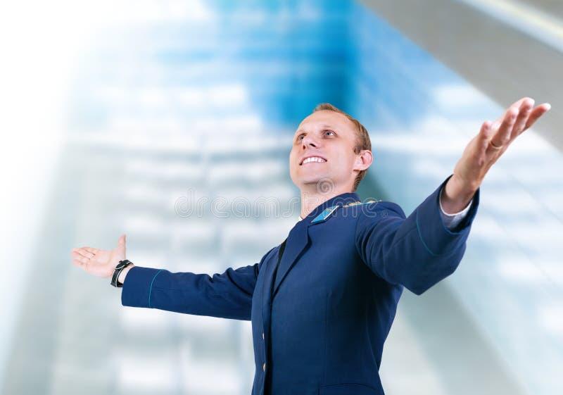Szczęśliwy młodego człowieka samolotu pilot nad szklanym nowożytnym budynkiem zdjęcie stock