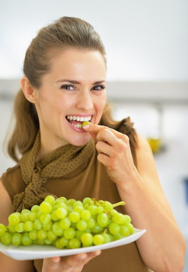 Szczęśliwy młodej kobiety łasowania winogrono zdjęcia stock