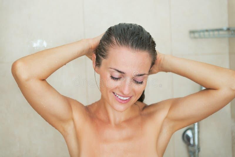 Szczęśliwy młodej kobiety domycie w prysznic zdjęcie stock