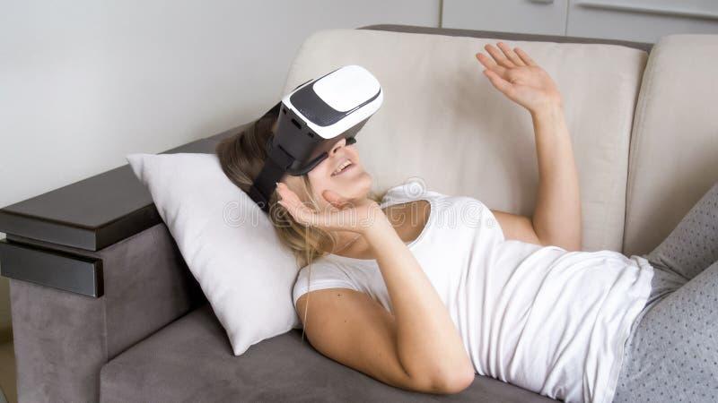 Szczęśliwy młodej kobiety lying on the beach na kanapie i używać rzeczywistości wirtualnej słuchawki obrazy stock