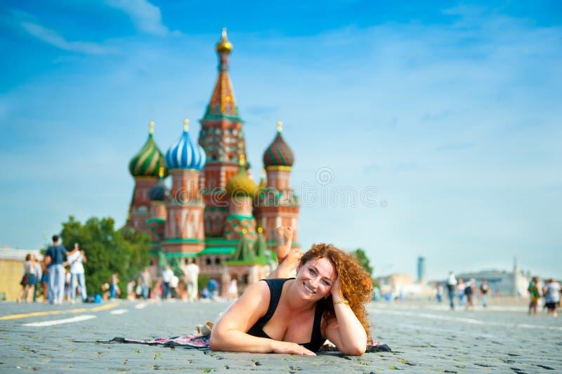 Szczęśliwy młodej kobiety lying on the beach na plac czerwony zdjęcia stock