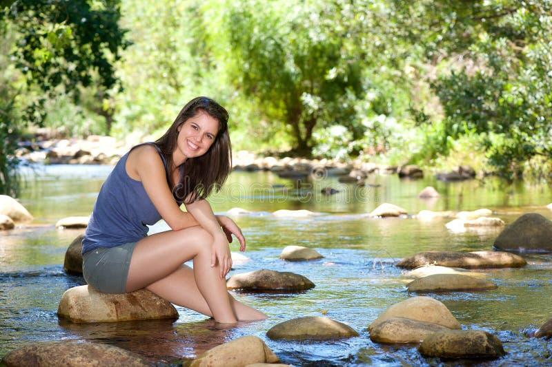 Szczęśliwy młodej kobiety obsiadanie strumieniem z ciekami w wodzie fotografia royalty free