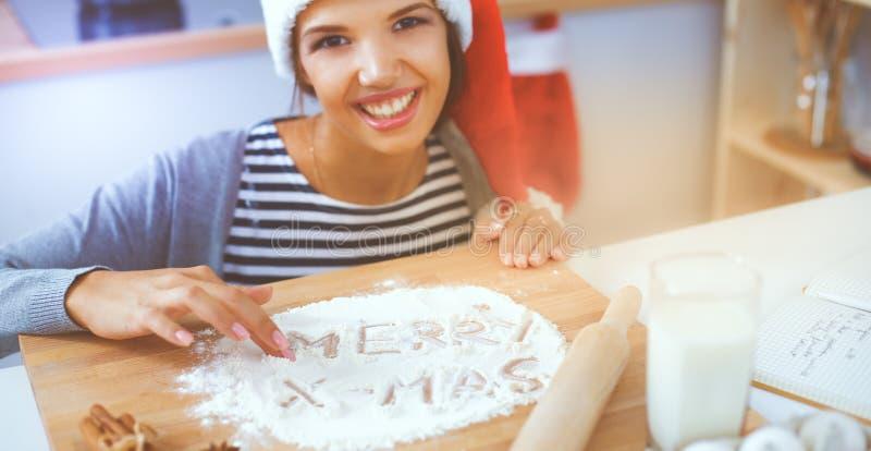 Szczęśliwy młodej kobiety ono uśmiecha się szczęśliwy mieć zabawę z Bożenarodzeniowymi przygotowaniami jest ubranym Santa kapelus zdjęcia royalty free