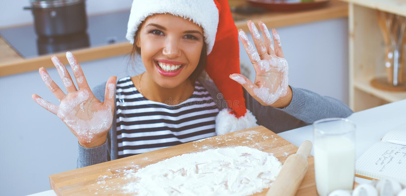 Szczęśliwy młodej kobiety ono uśmiecha się szczęśliwy mieć zabawę z Bożenarodzeniowymi przygotowaniami jest ubranym Santa kapelus fotografia stock