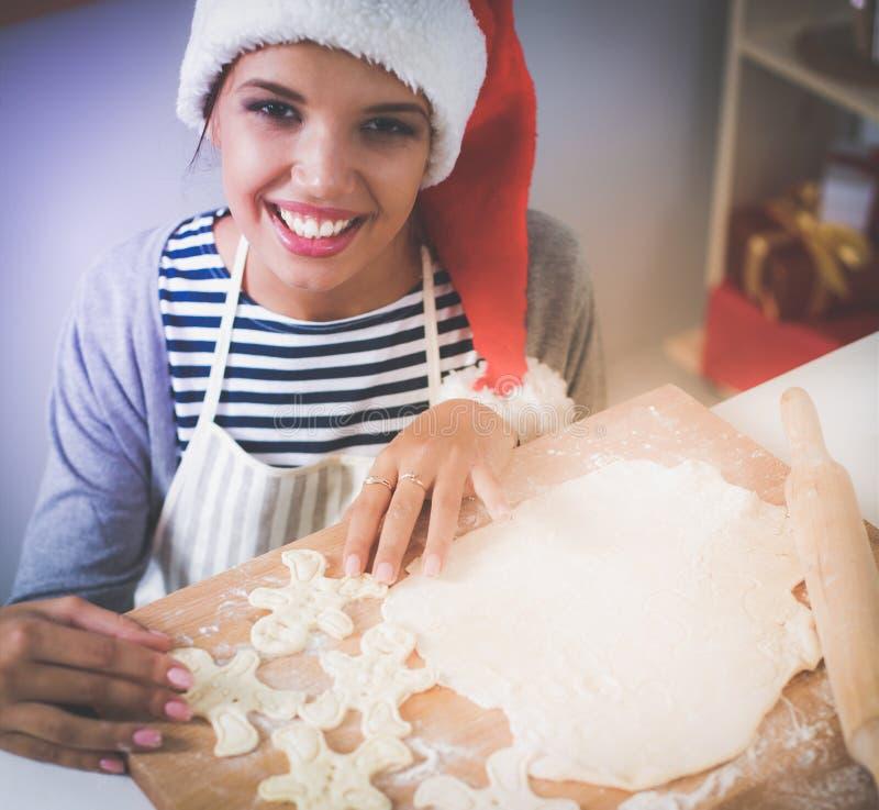 Szczęśliwy młodej kobiety ono uśmiecha się szczęśliwy mieć zabawę z Bożenarodzeniowymi przygotowaniami jest ubranym Santa kapelus obraz stock