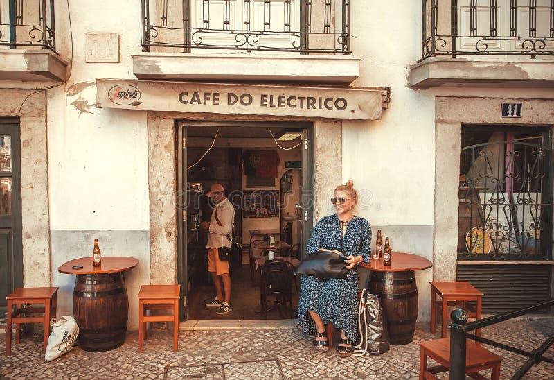 Szczęśliwy młodej kobiety pić piwny przy drzwi mały ulica bar i śmiać się zdjęcia royalty free